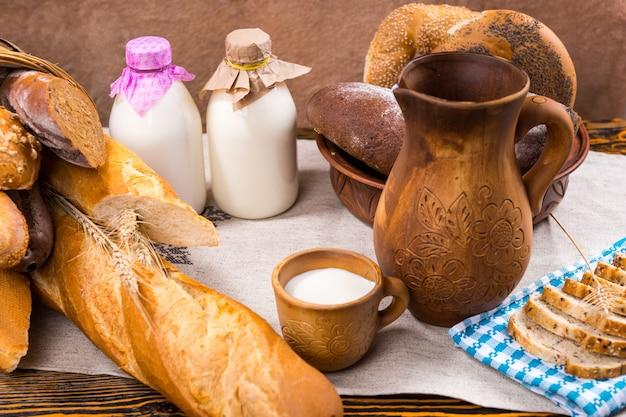 Kosz i miska bagietek i bajgli obok drewnianego dzbanka i filiżanki w pobliżu dwóch butelek mleka i tacy z krojonym chlebem
