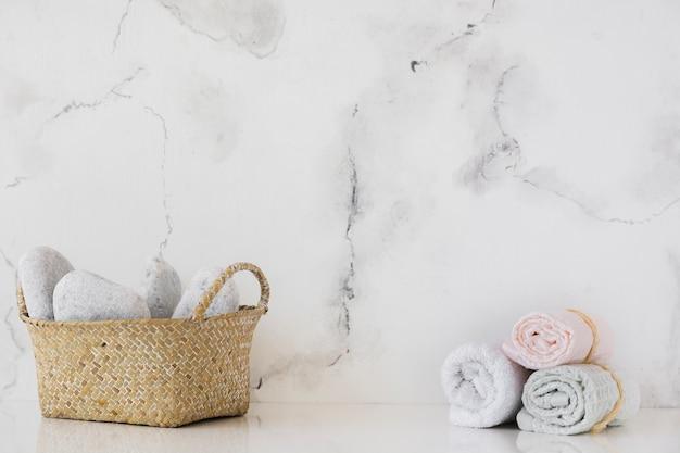Kosz i ręczniki na stole z marmurową backgrount i kopii przestrzenią