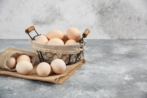 Kosz i worek ekologicznych świeżych niegotowanych jaj na marmurowej powierzchni.