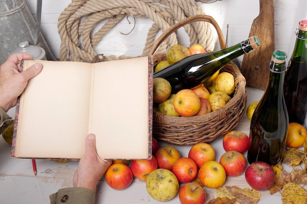 Kosz jabłek, butelki cydru i stary notatnik