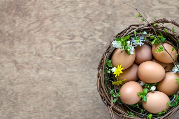 Kosz jajka na drewnianym tle z kopii przestrzenią. widok z góry. wielkanocna koncepcja.