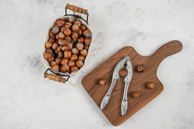 Kosz łuskanych orzechów laskowych i narzędzie do łamania orzechów obok deski do krojenia.
