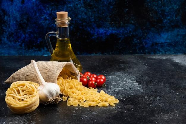 Kosz makaronu z oliwą z oliwek, pomidorkami koktajlowymi i czosnkiem dookoła.