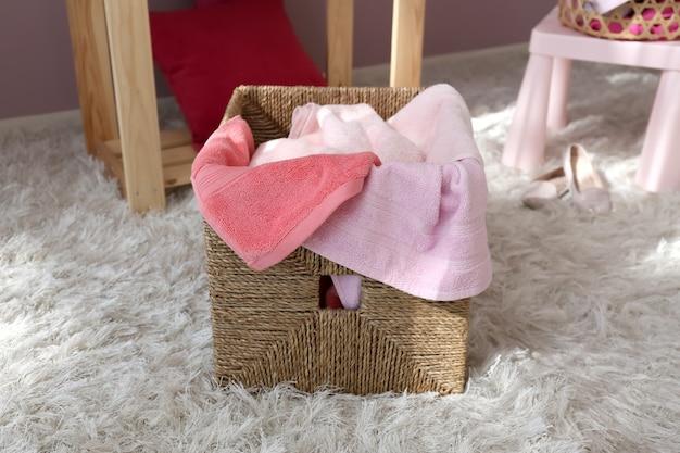 Kosz na bieliznę z brudnymi ręcznikami na podłodze