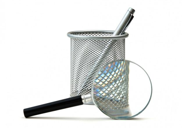 Kosz na ołówki i szkło powiększające na białym tle