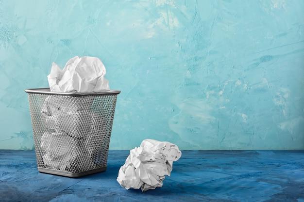 Kosz na śmieci z papierami, obok niego leży jedna bryła.