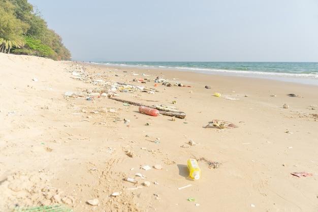 Kosz na tropikalnej plaży. problem środowiskowy zanieczyszczenia tworzywami sztucznymi. plastikowe butelki i inne śmieci wyrzucone na plażę.