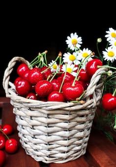 Kosz owoców z dojrzałymi wiśniami i kwiatami na ciemnym tle