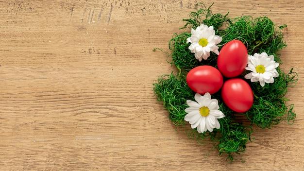Kosz ozdobiony kwiatami z jajkami w środku