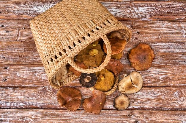Kosz pełen dużych grzybów na drewnianym stole