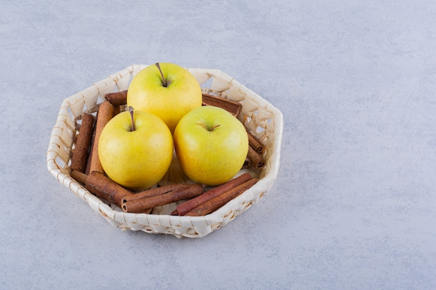 Kosz pełen laski cynamonu i jabłek na kamieniu.