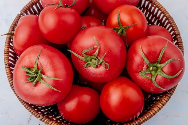 Kosz pełen pomidorów na białej powierzchni