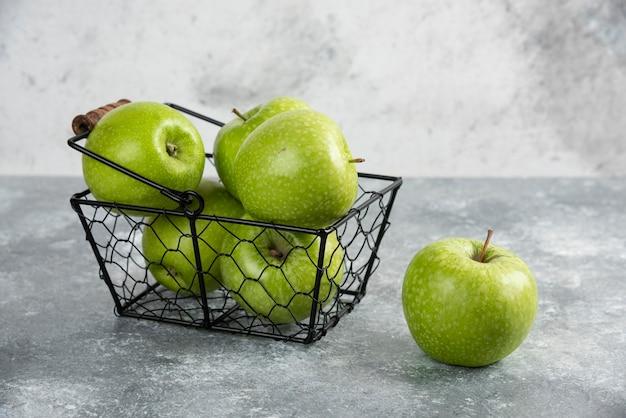 Kosz pełen zielonych błyszczących jabłek na marmurowym stole.
