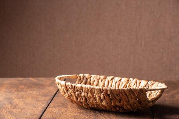 Kosz, piękny słomiany kosz umieszczony na rustykalnym drewnie i ciemnym tle, selektywne focus.