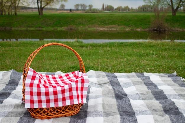 Kosz piknikowy na szarym kocu w kratkę w pobliżu rzeki z miejscem na kopię. koncepcja pikniku na świeżym powietrzu