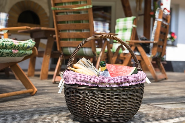 Kosz piknikowy wypełniony owocami i butelką