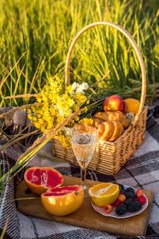 Kosz piknikowy z jedzeniem i kieliszkiem z szampanem na zielonym słonecznym trawniku.