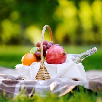 Kosz piknikowy z owocami, jedzeniem i wodą w szklanej butelce