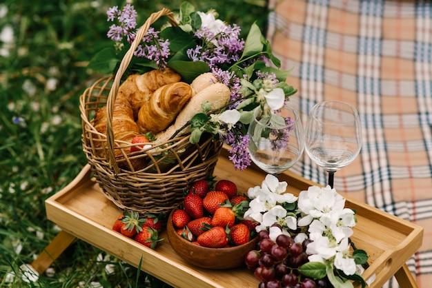 Kosz piknikowy z truskawkami, winogronami i bułeczkami na zielonej trawie w ogrodzie
