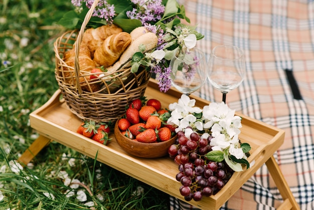 Kosz piknikowy z truskawkami, winogronami i bułkami na zielonej trawie w ogrodzie