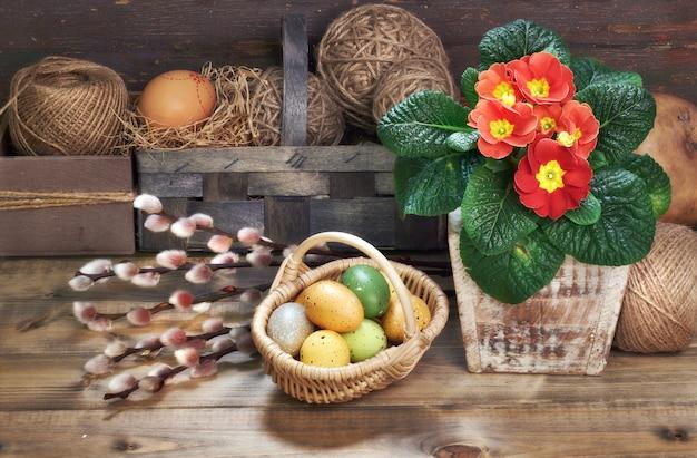 Kosz pisanki, czerwone kwiaty wiesiołka w doniczce na drewnianym stole