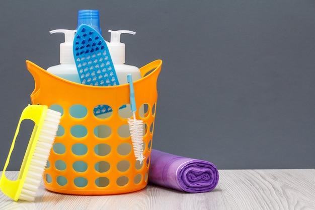 Kosz plastikowy z butelkami płynu do mycia naczyń, płynu do glazury, detergentu do kuchenek mikrofalowych i kuchenek. pędzle, worki na śmieci na szarym tle. zestaw do mycia i czyszczenia.