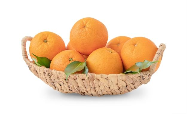 Kosz pomarańczy z zielonymi liśćmi na białym tle na białej powierzchni