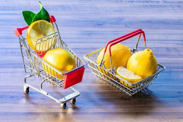 Kosz supermarketu i wózek supermarketu niosący zielony liść i cytrynę.