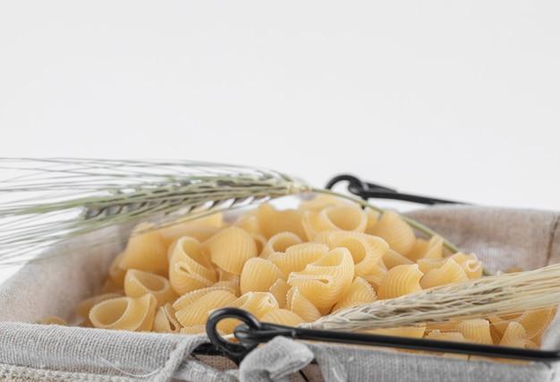 Kosz surowego makaronu z kłosami pszenicy na białym tle. zdjęcie wysokiej jakości