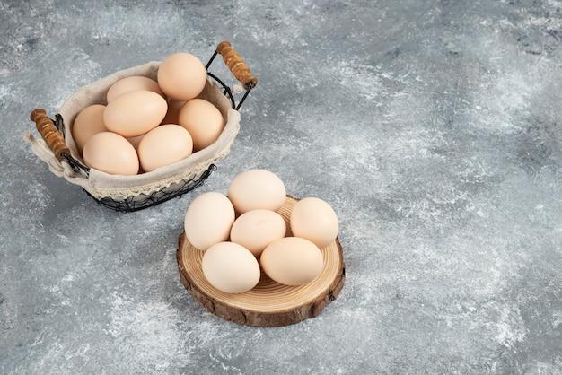 Kosz świeżych, niegotowanych jajek ekologicznych ułożony na marmurowej powierzchni.