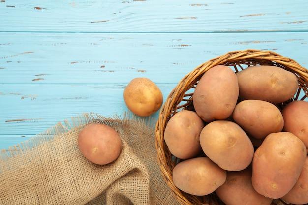 Kosz świeżych smacznych młodych ziemniaków na niebieskim tle. widok z góry