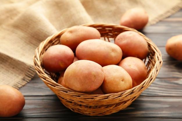 Kosz świeżych smacznych młodych ziemniaków na szarym tle. widok z góry
