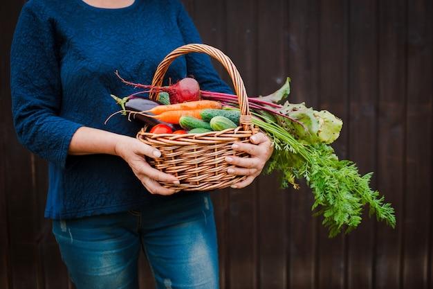 Kosz warzyw w rękach rolnika na drewnianym.