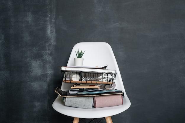 Kosz z artykułami biurowymi, złożonymi próbkami tekstyliów, dokumentami biznesowymi, laptopem i doniczką z małą zieloną roślinką na białym krześle