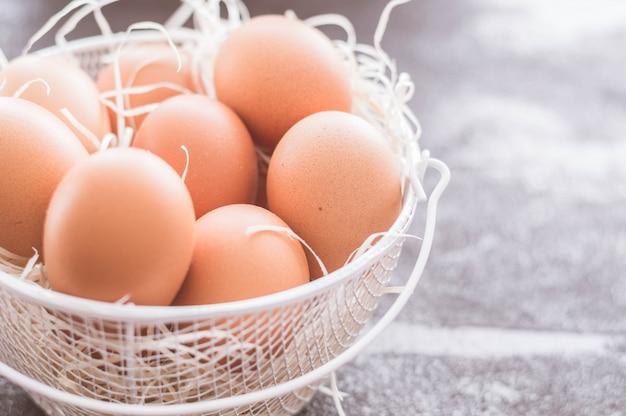 Kosz z białego metalu wypełniony brązowymi jajkami i pasmami słomy.