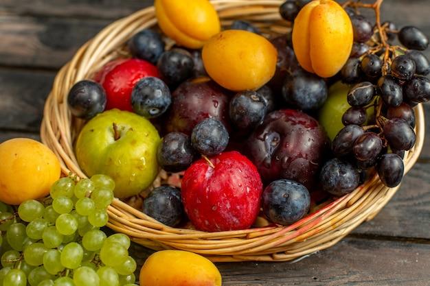 Kosz z bliska z owocami łagodnymi i kwaśnymi, takimi jak winogrona, morele, śliwki na brązowym rustykalnym owocu na biurku