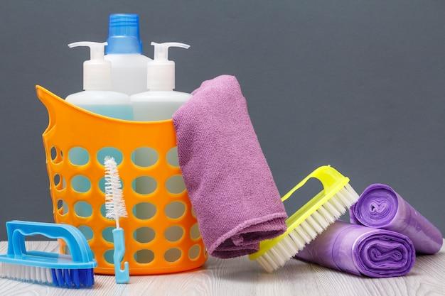 Kosz z butelkami płynu do mycia naczyń, płynu do glazury, detergentu do kuchenek mikrofalowych i kuchenek. pędzle, ręczniki, worki na śmieci na szarym tle. koncepcja mycia i czyszczenia.