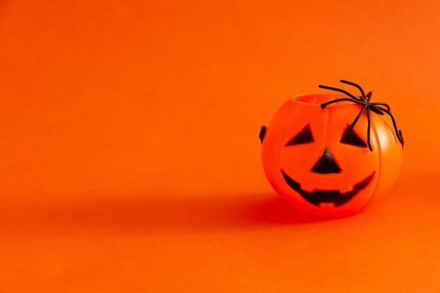 Kosz z cukierkami w kształcie dyni z lampionami na halloween na pomarańczowym tle z pająkiem