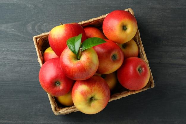 Kosz z czerwonymi jabłkami na ciemnym drewnianym stole
