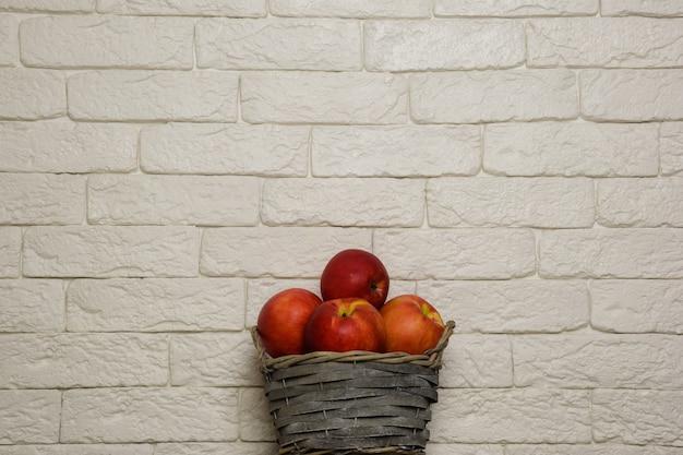 Kosz z czerwonymi jabłkami na tle ceglanej lekkiej ściany kosz znajduje się na dole pośrodku