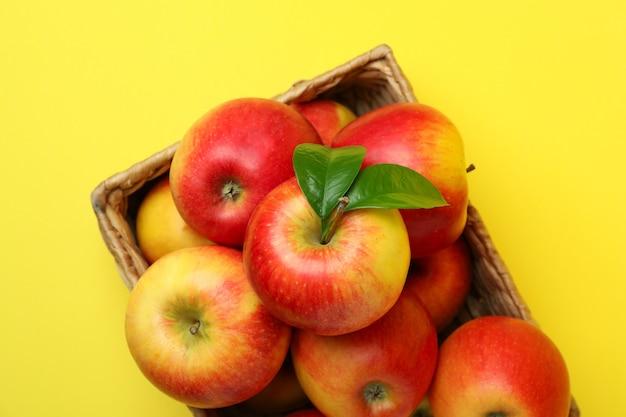 Kosz z czerwonymi jabłkami na żółtym tle