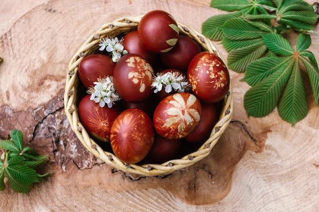 Kosz z czerwonymi jajkami wielkanocnymi na rustykalnym drewnianym stole