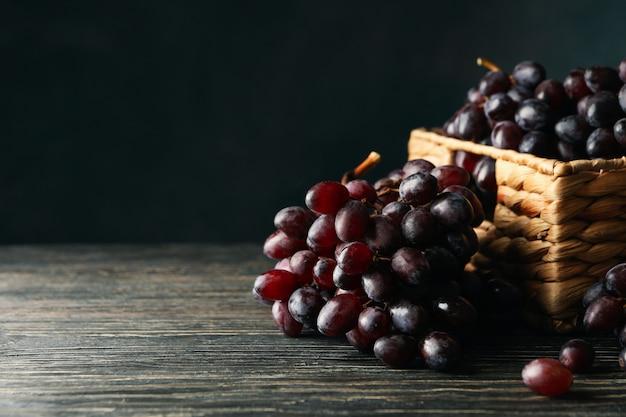 Kosz z dojrzałymi winogronami na drewnianym