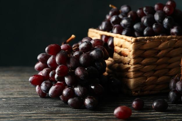 Kosz z dojrzałymi winogronami na drewnie