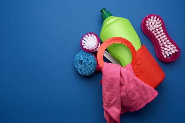 Kosz z gąbkami do mycia, szczotkami i środkiem czyszczącym w zielonej plastikowej butelce