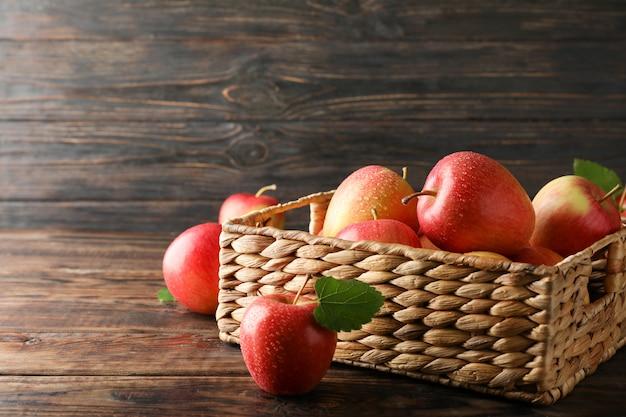Kosz z jabłkami na drewnianym stole