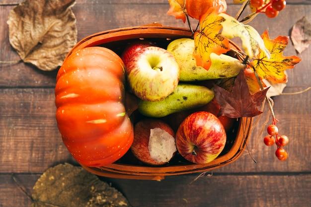 Kosz z jesiennymi żniwami na stole