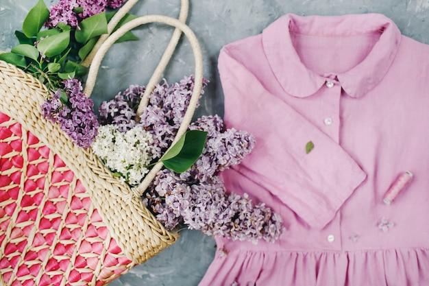 Kosz z kwiatami bzu i pastelowa różowa letnia sukienka