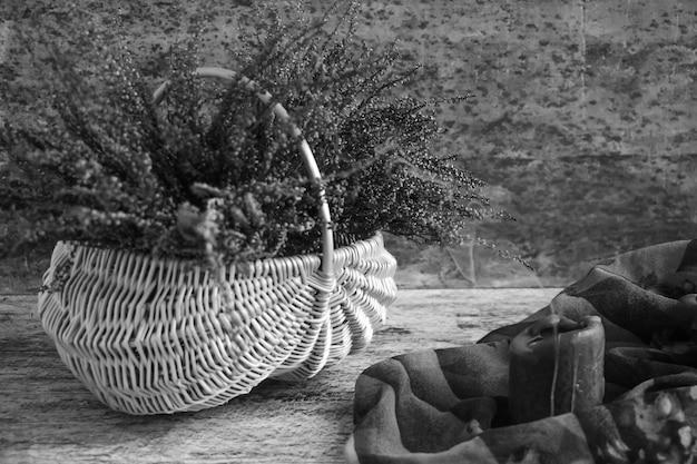 Kosz z kwiatami liliowego wrzosu i klimatycznymi świeczkami czarno-biała fotografia