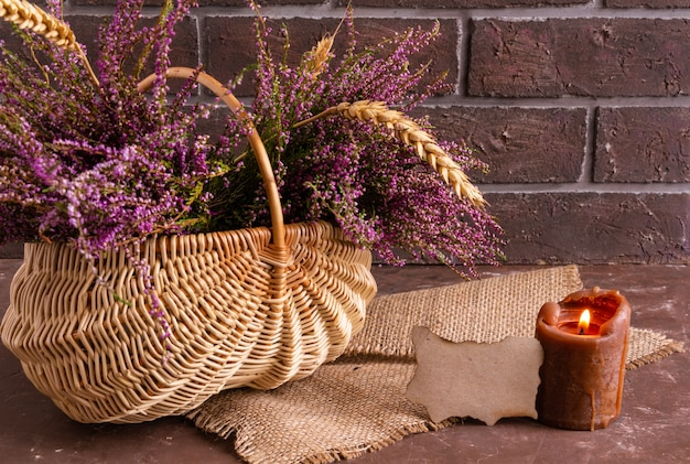 Kosz z kwiatami na brązowym tle liliowego wrzosu i klimatycznej przestrzeni do kopiowania świec
